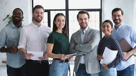trabalho em equipe : Happy proud confident professional multiethnic business people leaders employees company staff diverse people group smiling looking at camera standing in office together, corporate team portrait Vídeos