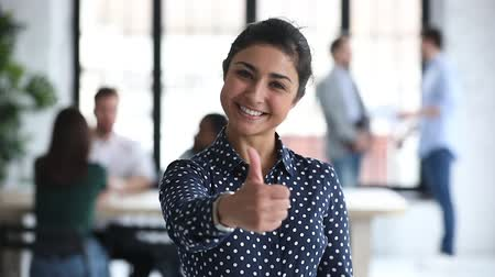 polegares : Happy smiling proud indian ethnic young businesswoman professional employer leader manager showing thumbs up hand like sign recommend corporate services concept looking at camera in office, portrait