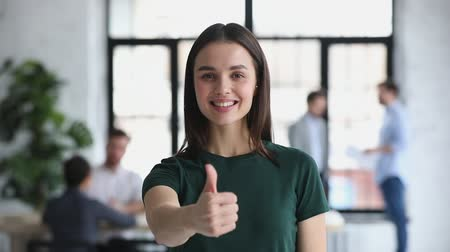 entusiasmo : Happy proud confident young professional business woman leader winner employee looking at camera showing thumbs up hand sign gesture in office recommend best job choice concept, closeup portrait