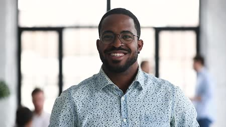 estagiário : Smiling african american young hipster businessman professional sales manager employee intern wear glasses looking at camera, happy millennial afro ethnic male office worker close up portrait