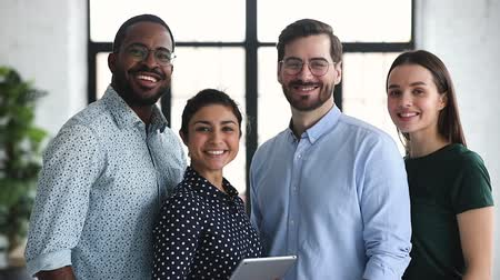 etnia africano : Smiling professional diverse corporate office business team members group look at camera, four happy proud confident multiracial leaders employees staff diverse people group stand together, portrait