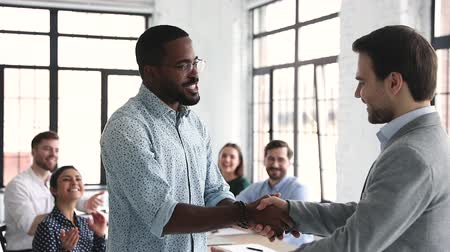 etnia africano : Proud confident african american male professional get promoted handshake boss pleased by multiracial team feedback applause, employee respect, recognition at work, staff reward concept, slow motion Stock Footage