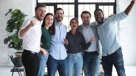 feliz : Overjoyed ecstatic diverse ethnic business team young colleagues group celebrate professional triumph together scream look at camera stand in office, staff achievement in corporate leadership concept