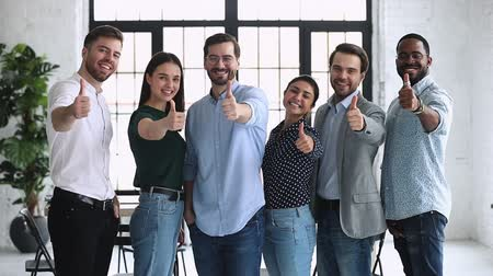 entusiasmo : Happy proud professional diverse business people group show thumbs up look at camera stand in row in office, human resource recommend vote for best business choice concept, corporate team portrait