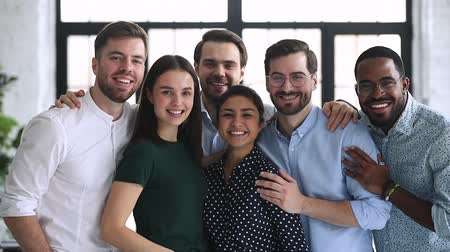 satysfakcja : Happy confident professional diverse team business people bonding stand in office looking at camera, smiling multiethnic corporate staff group portrait, partnership and teamwork concept, slow motion