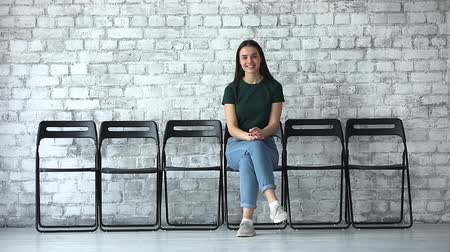 прокат : Happy confident female job applicant looking at camera sit alone on chairs, smiling millennial business woman graduate professional waiting for employment interview, leadership and recruit concept Стоковые видеозаписи
