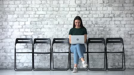 прокат : Smiling young businesswoman job seeker using laptop sit alone on chair wait for employment interview, happy millennial female professional candidate await with computer in recruit expectation concept
