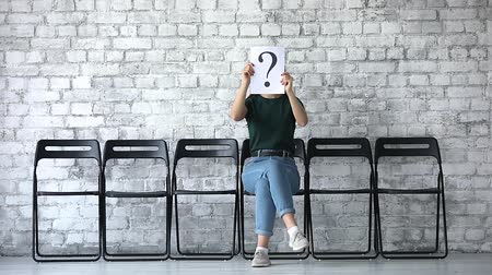 otázky : Jobless unemployed female job seeker hide face with question mark sit alone on chair row, professional business woman waiting for employment hiring interview, human resource and recruit concept