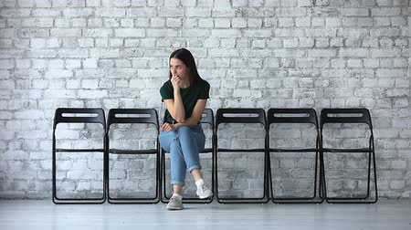 expectativa : Stressed millennial business woman graduate intern wait for job interview sit alone on chair, worried unemployed young female professional vacancy candidate search work, employment recruit concept