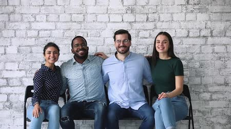 прокат : Happy professional diverse corporate office business group bonding looking at camera sitting on chairs, four happy proud confident multiethnic team people portrait, human resource, teamwork concept