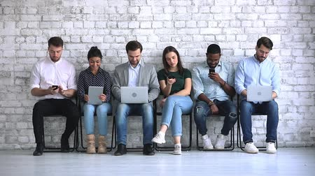 прокат : Six multiracial young business people sit on chairs in row waiting for job interview using tech electronic devices, diverse ethnic group obsessed with gadgets addicted digital life, recruit concept Стоковые видеозаписи