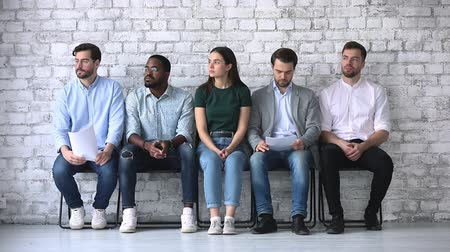 expectativa : Stressed diverse ethnicity business people applicants waiting for their turn preparing for job interview sit in line queue on chairs, human resources and recruitment, rivalry in job search concept Vídeos