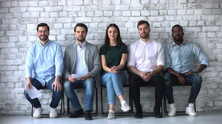 rekrutacja : Happy confident diverse ethnicity business people applicants look at camera sit on chairs, five smiling millennial professionals wait for employment job interview, recruit and human resource concept