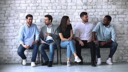 прокат : Happy friendly multiracial business people job applicants sit on chairs in row talking, five professionals group communicate while wait for employment interview, human resource relationship concept