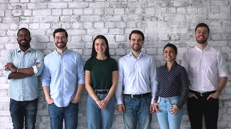 etnia africano : Six happy multi ethnic professional business people stand in row near brick wall look at camera, smiling diverse young human resource corporate staff group team portrait, hr concept, slow motion