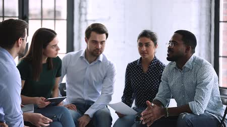 man in office : Friendly creative multiethnic marketing team people brainstorming share ideas talking working together in teamwork discuss new project plan sit on chairs in circle office at group corporate meeting