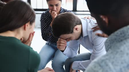 psychotherapist : Sad desperate crying addicted alcoholic man share problem grief during group therapy session, diverse people helping supporting male patient having trauma depression at psychotherapy meeting concept Stock Footage