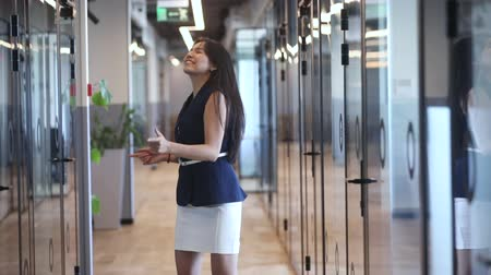 chodba : Excited young asian female employee walking alone in modern office, starting dancing, feeling joyful, celebrating promotion, money reward, business success or achievement, while nobody watching.