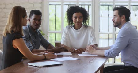 etnia africano : Confident young african american boss company owner holding brainstorming meeting with motivated diverse top management in office. Focused mixed race coworkers discussing project details at workplace.