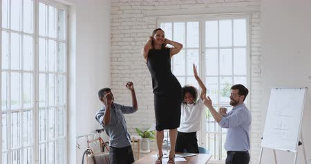 etnia africano : Excited young diverse business people having fun together in office, watching overjoyed female colleague dancing on table. Happy multiracial startup entrepreneurs celebrating corporate success. Stock Footage