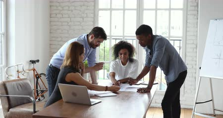 workgroup : Creative young multiethnic teammates analyzing paper reports together in office. Concentrated business people writing remarks on research results, developing company marketing strategy at meeting. Stock Footage