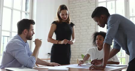 dokumentum : Focused young female marketing analyst explaining research results to mixed race teammates in office. Concentrated successful multiracial business people developing strategy at brainstorming meeting. Stock mozgókép