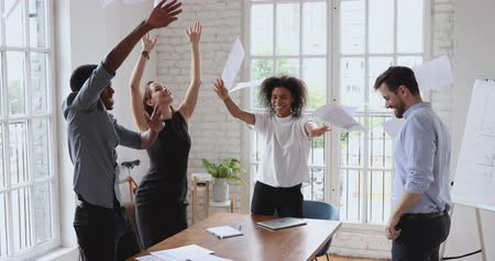 etnia africano : Happy multiracial business people with papers in hands having fun, throwing documents in air, celebrating company success while excited young manager in eyewear climbing dancing on table at office.