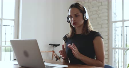 çözme : Smiling confident young female financial advisor wearing wireless headphones, looking at computer screen, consulting clients online, sending documents. HR manager holding job interview with applicant. Stok Video