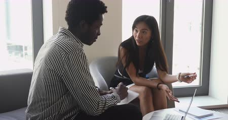 odaklanma : Skilled young asian leader explaining corporate software application to attentive african american intern. International teammates discussing project report or research results together at office. Stok Video