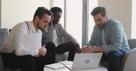 discutir : Young businessman in eyewear sitting on chairs with diverse male partners at office, showing project presentation on computer. Successful millennial managers entrepreneurs discussing business ideas.
