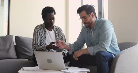 etnia africano : Confident businessman in eyeglasses explaining project details to young mixed race employee. Millennial skilled african american intern consulting with professional mentor coach trainer at office. Stock Footage
