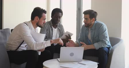 etnia africano : Motivated young multiracial businessmen sitting on armchairs, looking at computer screen, discussing startup project presentation, research results or developing growth strategy together at office. Stock Footage