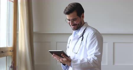 ped : Smiling male professional medic doctor surgeon wear white uniform stethoscope holding using digital tablet computer check medical data stand alone in hospital office, healthcare technology concept