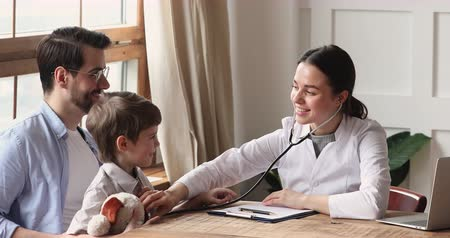 paediatrician : Smiling female pediatrician hold stethoscope exam preschool child boy patient visit doctor with dad, doctor listen kid heartbeat do pediatric checkup sit at table, children medical healthcare concept