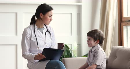 paediatrician : Friendly woman pediatrician and cute shy kid boy patient talk at pediatric checkup, female doctor nurse having trust conversation with preschool child about healthcare at medical consultation concept Stock Footage