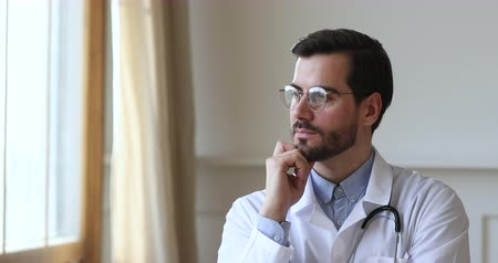 çözümler : Successful thoughtful happy confident young male professional medic doctor practitioner wear white medical coat glasses stethoscope look through window dreaming think planning future career concept