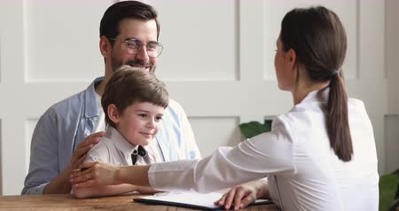 paediatrician : Caring kind professional female pediatrician consulting stroking child boy giving high five to happy healthy cute preschool patient visiting doctor with father, paediatric medical healthcare concept