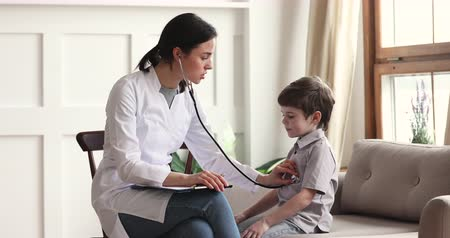 paediatrician : Young female doctor pediatrician nurse wear white coat listening heartbeat exam cute little patient child boy using stethoscope on pediatric checkup appointment, children medical healthcare concept