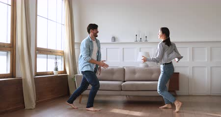 befektetés : Happy carefree active young couple dancing in living room at home, funny husband and wife first time home owners having fun enjoy party together in modern apartment, mortgage and freedom concept Stock mozgókép
