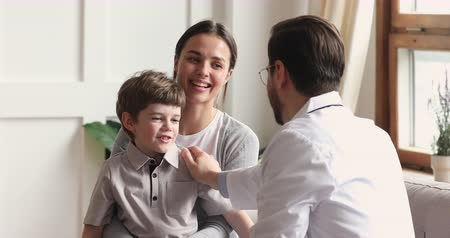 paediatrician : Happy healthy brave cute little boy sit on mom lap give high five to caring male surgeon doctor pediatrician show good attitude give support to kid patient visit pediatric checkup meeting in hospital