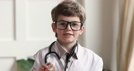 przedszkolak : Happy funny adorable cute little preschool child boy wear white medical coat glasses holding stethoscope looking at camera playing doctor alone, children future professions concept, closeup portrait Wideo