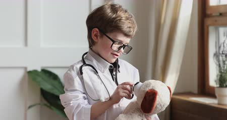 любопытство : Funny small preschooler boy wear medical coat glasses hold stethoscope pretend listen toy dog patient, cute adorable little smart child play hospital game as vet doctor, children veterinary concept
