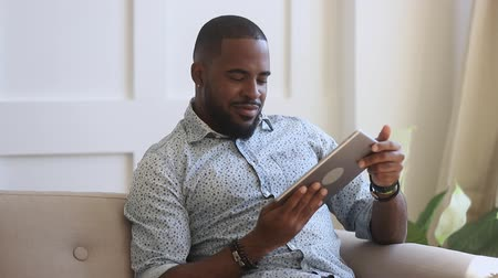 leisure time : Smiling biracial young guy enjoying leisure weekend time, using digital tablet at home. Happy african american man playing online games, watching funny videos, swiping photos, chatting with friends.