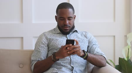 webseite : Surprised young african american man looking at mobile phone screen, receive win notification, amazed by good news, sitting alone at home. Biracial guy excited by unexpected victory success.