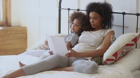 deitado : Little energetic child girl lying on bed with african mommy, listening to disinteresting story. Pleasant biracial woman reading book to bored small preschool daughter, relaxing together in bedroom.