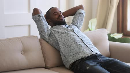 harmonie : Calm carefree smiling african ethnicity young man relaxing on cozy sofa with closed eyes alone at home. Happy peaceful mixed race enjoying leisure time, daydreaming, meditating, breathing fresh air.