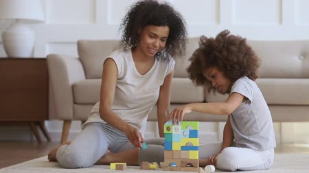 construtor : Full length happy african american woman sitting on carpet, playing with little cute daughter. Smiling biracial mom nanny helping small kid building castle with colorful wooden blocks constructor.