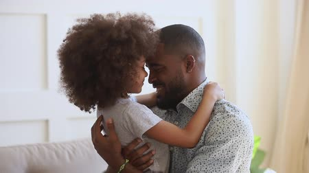 milující : Happy young african ethnicity father cuddling hugging embracing little cute daughter, looking at camera. Bonding loving mixed race dad touching noses with kid, laughing, having fun together at home. Dostupné videozáznamy