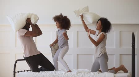 três pessoas : Overjoyed little african ethnicity child girl fighting pillows with happy parents on bed. Excited playful mixed race family of three in pajamas enjoying funny morning activity together in bedroom.