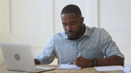 warsztat : Concentrated young african ethnicity guy sitting at table, watching educational webinar, writing down notes, rewinding video. Focused mixed race male freelancer working remotely at home or office. Wideo